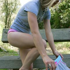 Young teen girl undressing in park