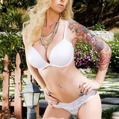 Brooke Banner tattooed arm Penthouse blue sky trimmed blonde garden pornstar